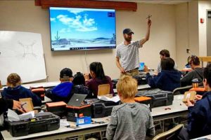 Matthew Westhoff, a pilot with UAF's ACUASI, teaches students about drones at a camp in June. Photo by Patty Eagan.